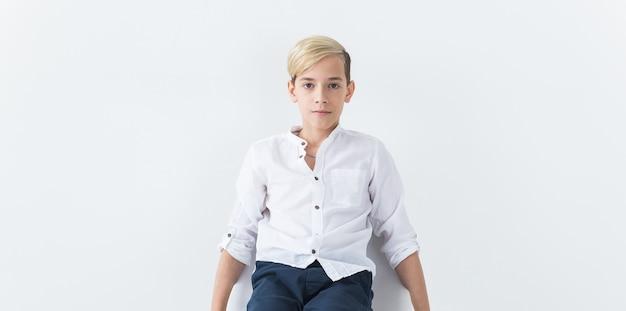 Conceito de solidão, solidão e tédio - estudante adolescente entediado, sentado em uma cadeira da escola, isolada no fundo branco, com espaço de cópia.