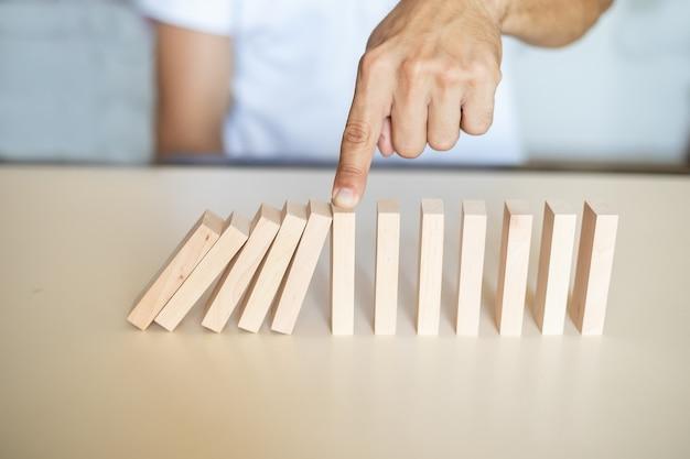 Conceito de solução com a mão impedindo que os blocos de madeira caiam na linha do dominó