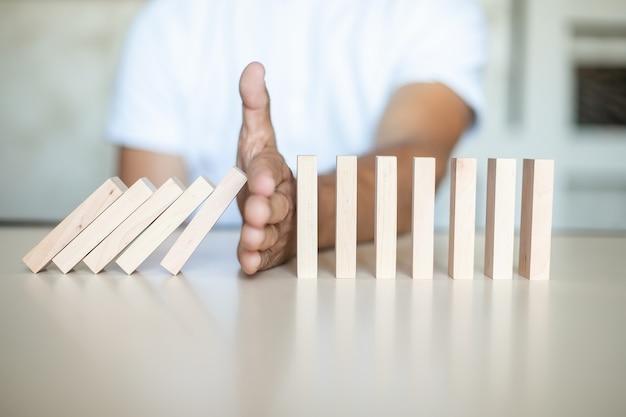 Conceito de solução com parada manual de blocos de madeira de cair na linha de dominó