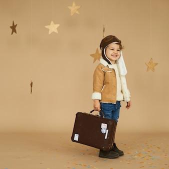 Conceito de sonhos e viagens. criança piloto aviador com um avião de brinquedo e mala joga em uma superfície bege