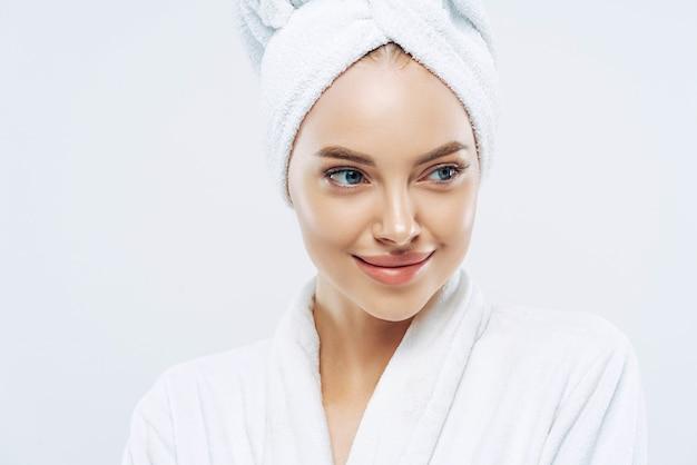 Conceito de spa, beleza e frescor de dia. mulher européia pensativa com pele saudável concentrada de lado pensativamente, sentindo-se revigorada após os procedimentos do banho, vestida de roupão, toalha na cabeça