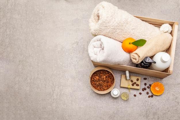 Conceito de spa café e tangerina. toalhas, óleo, esfoliante, sabão, loção. ingrediente natural, caixa de madeira.