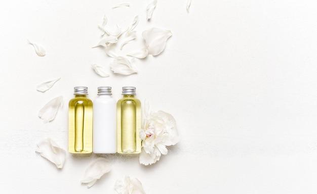 Conceito de spa com óleos de massagem decorados com pétalas de flores brancas.