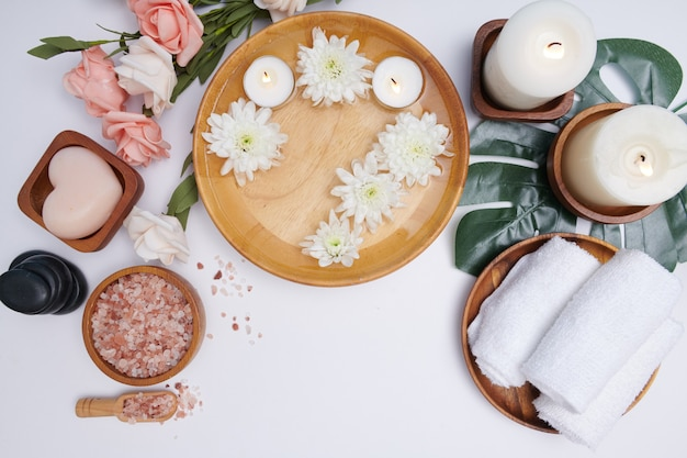 Conceito de spa. conceito de beleza e moda com conjunto de spa. água de flores perfumadas. relaxamento e zen, configuração de spa plana lay com tigela, sal de banho e flores, toalha e sabonete natural. vista do topo.