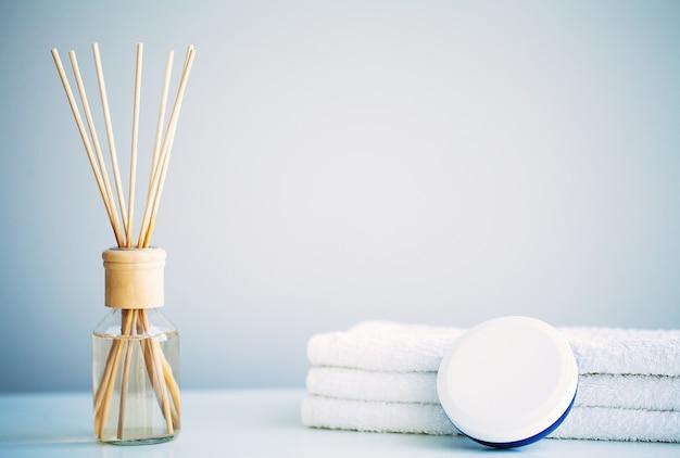 Conceito de spa. creme hidratante, toalhas e óleo aromático na mesa do banheiro.