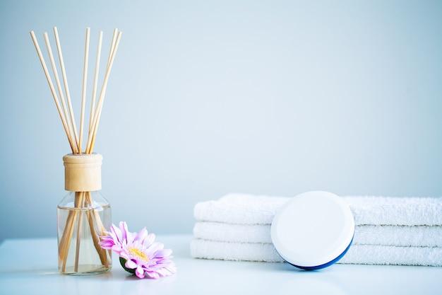 Conceito de spa, creme hidratante, toalhas e óleo de aroma na mesa na sala de banho