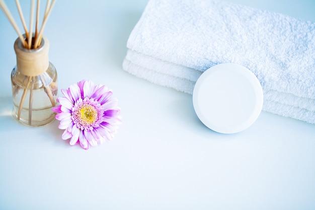 Conceito de spa. creme hidratante, toalhas e óleo de aroma na mesa na sala de banho