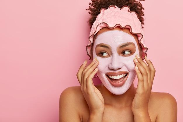 Conceito de spa e cuidados com a pele. mulher afro-americana satisfeita aplica máscara nutritiva de argila no rosto, tem expressão alegre, olha para o lado esquerdo, toca a bochecha, luta com problema de pele seca, tem corpo em topless
