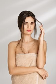 Conceito de spa. mulher coberta com toalha, segurando o fio de cabelo.