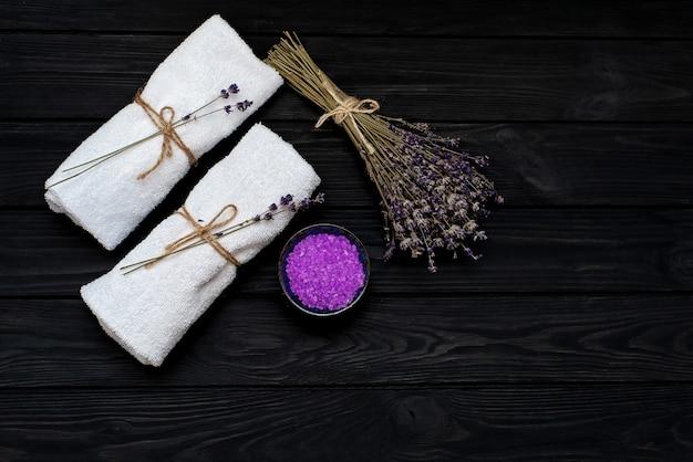 Conceito de spa. sal de lavanda para um banho relaxante, toalhas brancas e flores de lavanda secas em um fundo preto de madeira. aromaterapia plana leigos.