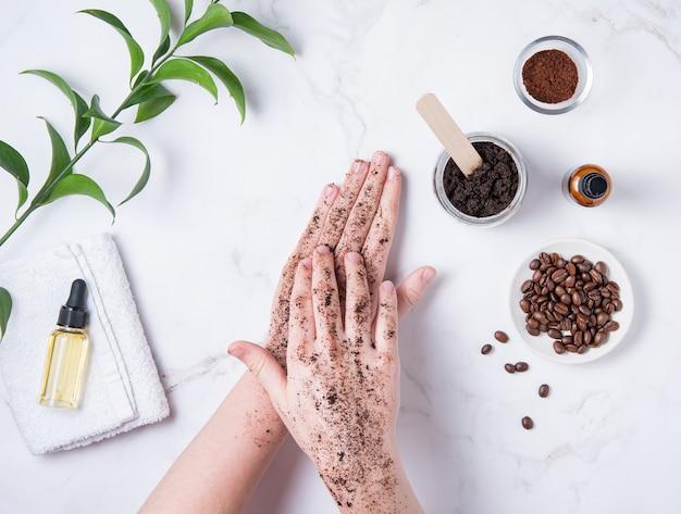 Conceito de spa. uma jovem faz uma massagem nas mãos com uma esfoliação caseira de café em cápsula reciclada com azeite sobre fundo de mármore. vista do topo
