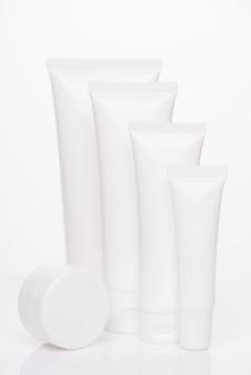Conceito de spf do tratamento do corpo da terapia do recipiente da caixa. foto vertical da coleção de dispensador de tamanho mínimo de tubos com colágeno vazio de rótulo em branco isolado sobre fundo branco de cor pura