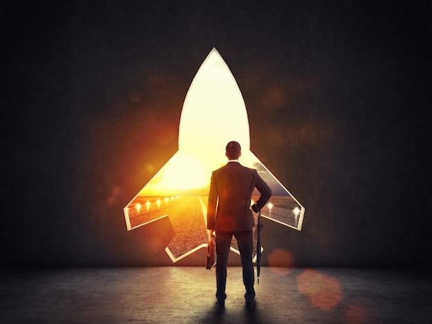 Conceito de startup com furo em forma de foguete na parede que alude à saída em direção a novos objetivos