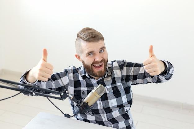 Conceito de streamer de apresentador de rádio e blogger - homem gesticulando thum sobre um fundo branco, apresentador de rádio