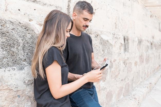 Conceito de streaming com casal encostado a parede