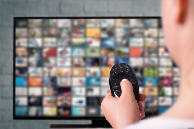 Conceito de streaming multimídia. mulher detém o controle remoto. tela de tv com muitas fotos. conceito de provedor de conteúdo vod