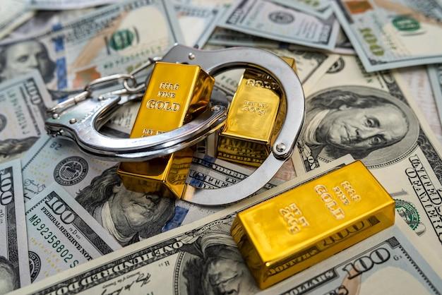 Conceito de suborno de barras de ouro e algemas em notas de dólar