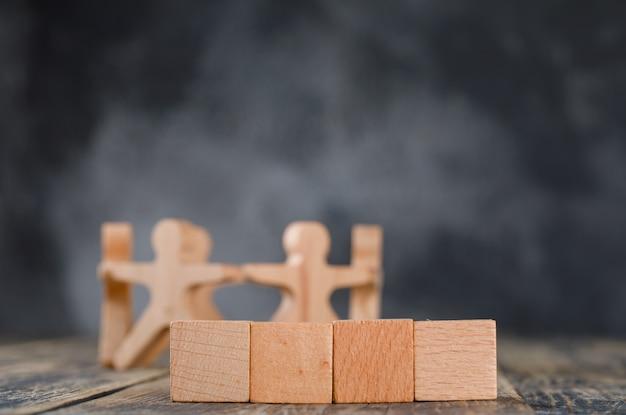 Conceito de sucesso comercial e trabalho em equipe com figuras de madeira de pessoas, vista lateral de cubos.