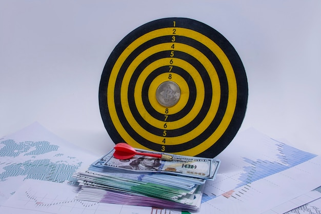 Conceito de sucesso e cumprimento de metas. jogo de dardos redondo com um maço de dólares, euros e uma moeda bitcoin no centro do círculo contra o fundo de gráficos e diagramas no papel.