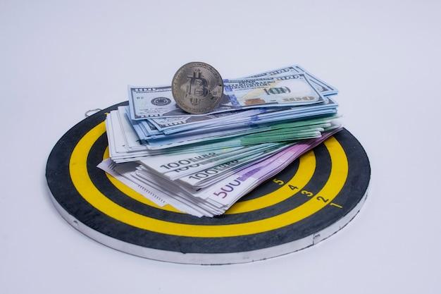 Conceito de sucesso e cumprimento de metas. jogo de dardos redondo com um maço de dólares, euros e uma moeda bitcoin no centro do círculo.