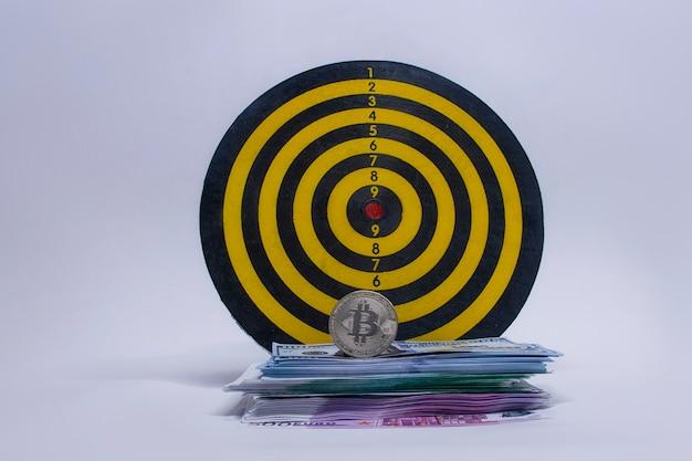 Conceito de sucesso e cumprimento de metas. jogo de dardos redondo com um maço de dólares, euros e uma moeda bitcoin.
