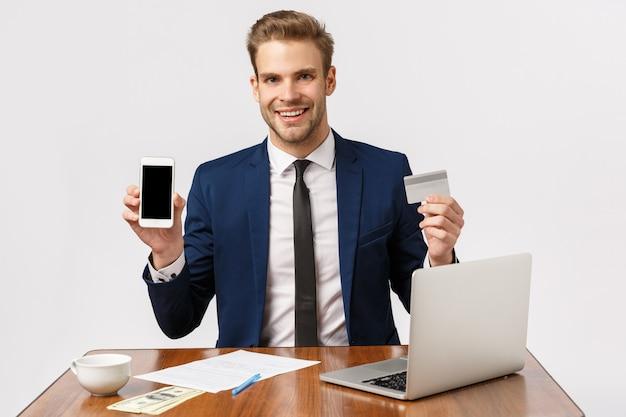 Conceito de sucesso, riqueza e finanças. bonito animado jovem empresário, empresário masculino no escritório, sentado a mesa com dinheiro, laptop e copo, segurando o cartão de crédito, mostrando a tela do smartphone
