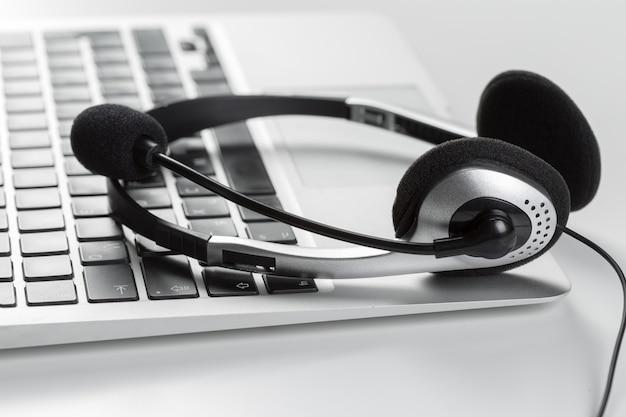Conceito de suporte de call center. fone de ouvido no laptop do computador teclado