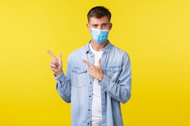 Conceito de surto de pandemia de covid-19, estilo de vida durante o distanciamento social do coronavírus. cara carrancuda preocupada e chateado, usando máscara médica e apontando o dedo no canto superior esquerdo no banner de informação.
