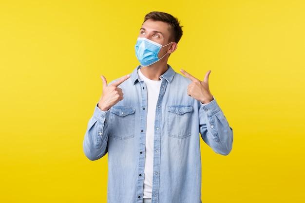 Conceito de surto de pandemia de covid-19, estilo de vida durante o distanciamento social do coronavírus. cara loiro bonito olhando no canto superior esquerdo e usando máscara médica antes de entrar no shopping.