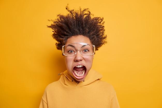 Conceito de surto emocional. mulher de pele escura e chocada, louca e chocada, grita olhares excitados de terror, ficando super irritada e indignada usando grandes óculos transparentes e camiseta