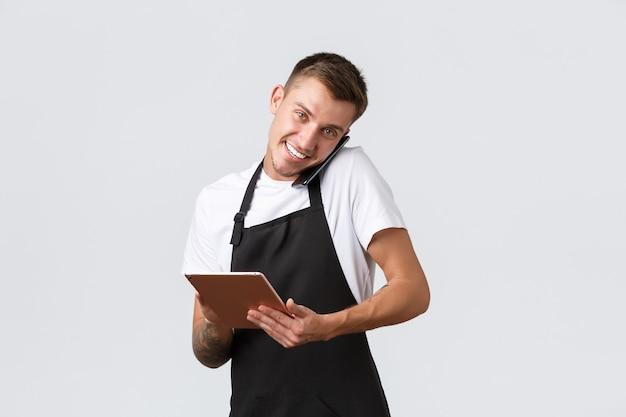 Conceito de take-away de lojas de varejo, pequenas empresas, cafés e restaurantes. gerente de loja jovem e bonito, funcionário recebendo pedidos por telefone, conversando com o cliente e anotando informações em um tablet digital