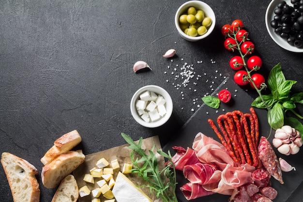 Conceito de tapas. presunto, chouriço de salsicha, azeitonas, tomate cereja, rúcula, queijo manjericão e queijo brie em uma placa de ardósia preta. conceito de antepastos.