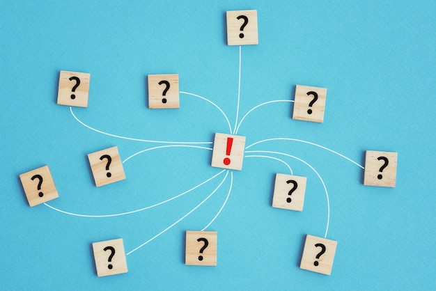 Conceito de tarefa de liderança e solução. blocos de madeira com pontos de interrogação conectados ao ponto de exclamação no fundo azul