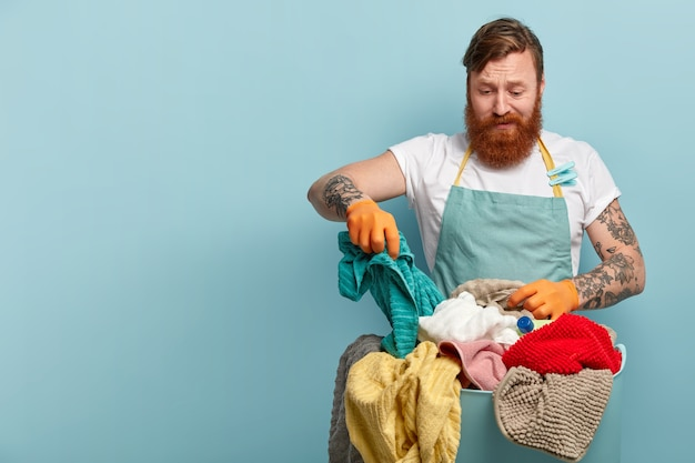 Conceito de tarefas domésticas e tarefas. homem barbudo ruivo e frustrado segurando uma toalha e escolhendo roupas sujas na cesta