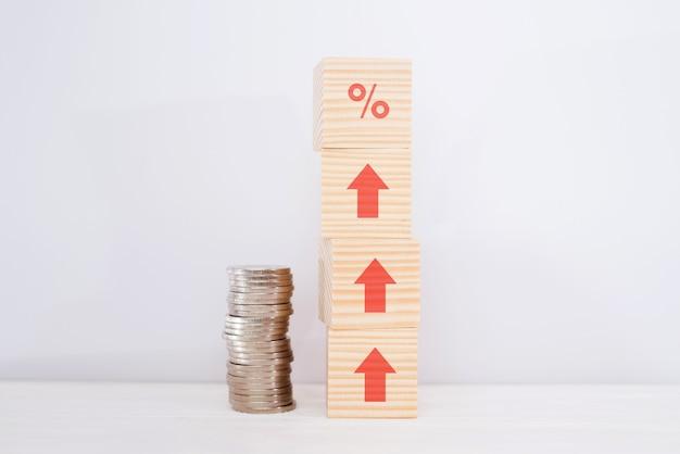Conceito de taxas financeiras e hipotecas de taxa de juros. bloco de cubos de madeira aumentando na parte superior com o símbolo de porcentagem do ícone e a seta na direção para cima