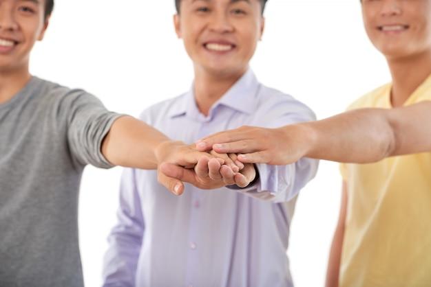 Conceito de teambuilding, três homens cortados, empilhando as mãos