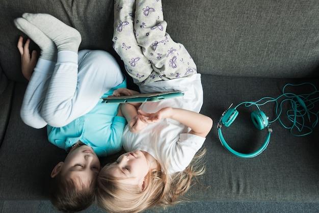 Conceito de tecnologia com crianças deitado no sofá