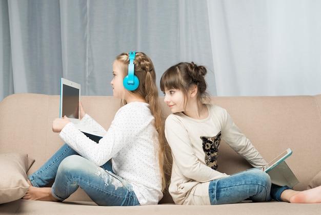 Conceito de tecnologia com meninas no sofá