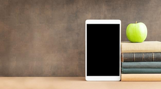 Conceito de tecnologia conceito de educação o tablet com tela preta e uma pilha de livros e maçã verde perto do quadro-negro