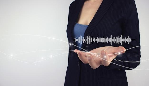 Conceito de tecnologia de áudio audiobook. mão segure a onda da trilha sonora do holograma digital em fundo cinza. editando e produzindo arquivos de áudio no pc