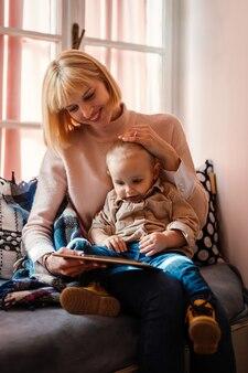 Conceito de tecnologia de família feliz. mãe sorridente e filho pequeno brincando com tablet digital em casa