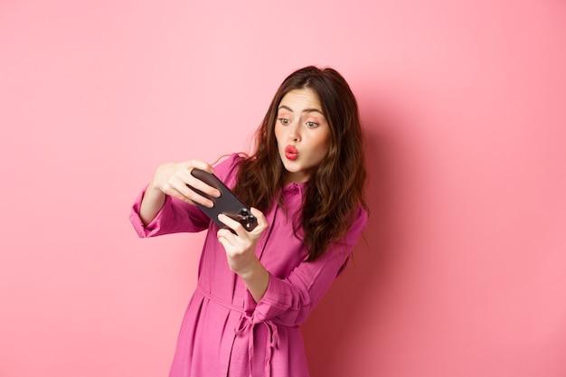 Conceito de tecnologia. despreocupada jovem inclinar o corpo, segurando o smartphone horizontalmente, jogando videogame no telefone, de pé contra a parede rosa.