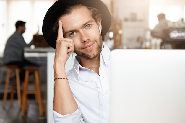 Conceito de tecnologia e comunicação. jovem elegante com barba e chapéu preto, ouvindo música em fones de ouvido brancos, sentado em frente a um laptop genérico, apoiado no cotovelo e sorrindo