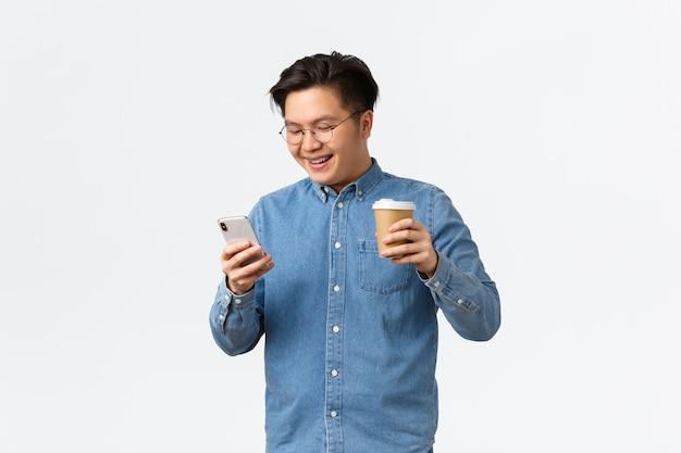 Conceito de tecnologia e lazer de estilo de vida sorrindo estudante universitário homem asiático, tendo pausa para beber tak ...