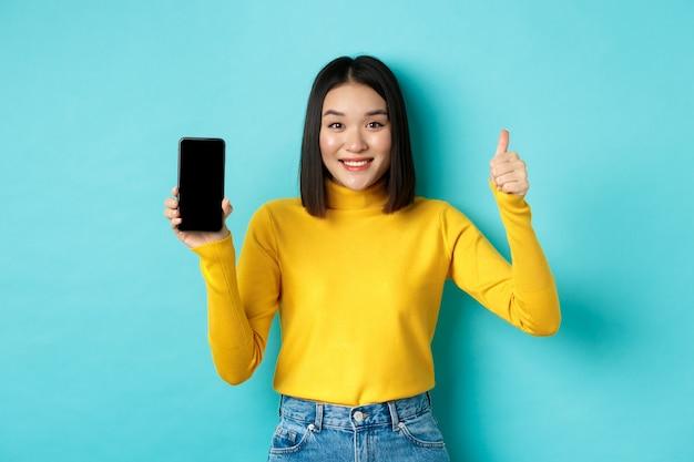 Conceito de tecnologia e pessoas. alegre menina asiática com suéter amarelo, mostrando a tela do smartphone em branco e polegares para cima, demonstra a oferta online, de pé sobre um fundo azul.
