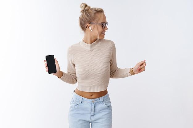 Conceito de tecnologia, estilo de vida e música. retrato de uma mulher loira elegante, bonita e despreocupada, usando fones de ouvido sem fio, dançando, cantando e se divertindo, segurando um smartphone