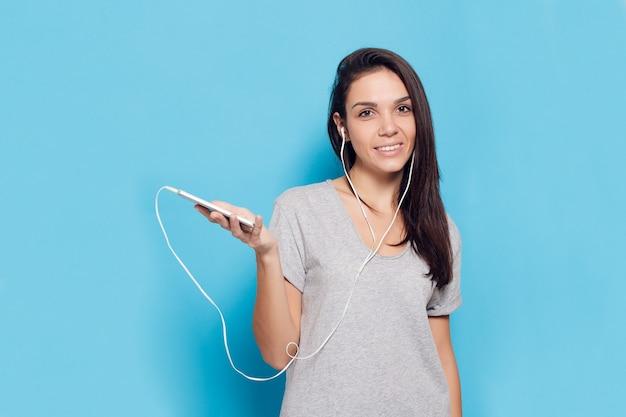 Conceito de tecnologia, estilo de vida, vício em internet e pessoas - jovem mulher bonita com telefone inteligente. mulher alegre com fones de ouvido em um fundo azul. mulher atraente feliz e sorridente
