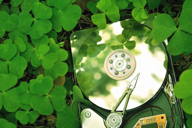 Conceito de tecnologia favorável ao meio ambiente; disco rígido na grama da floresta; foco no disco rígido