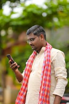 Conceito de tecnologia: fazendeiro indiano usando smartphone