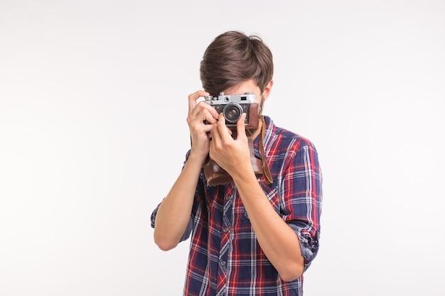 Conceito de tecnologia, fotografia e pessoas - homem bonito em camisa xadrez, tirando uma foto na câmera retro.